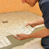 Man installing ceramic tiles on shower floor